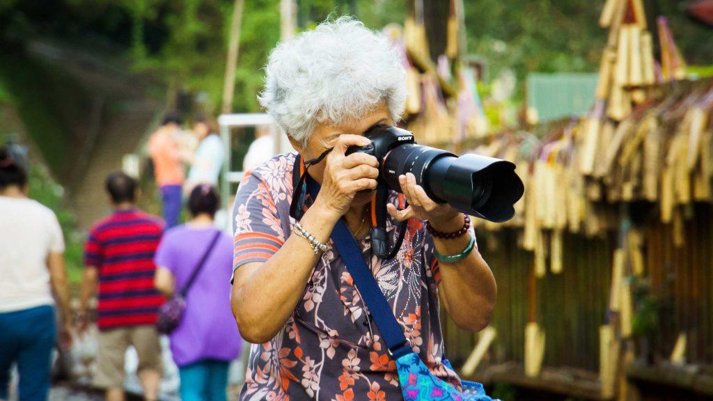Anziana in vacanza che scatta delle foto